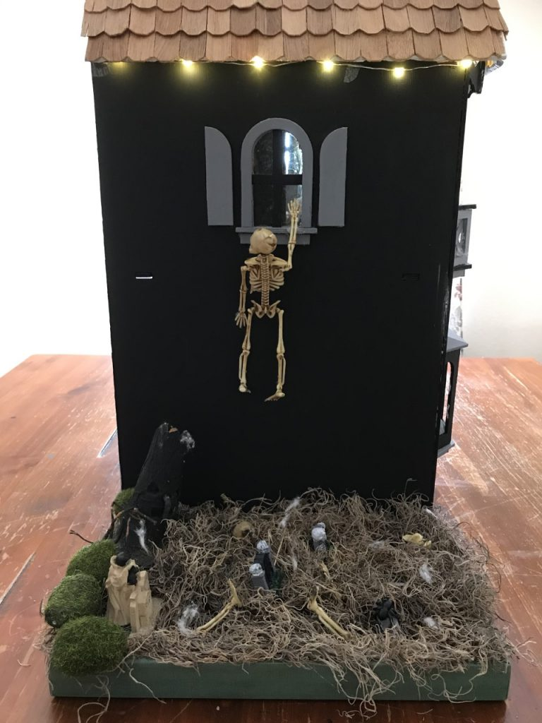 A skeleton tries to climb into this haunted dollhouse
